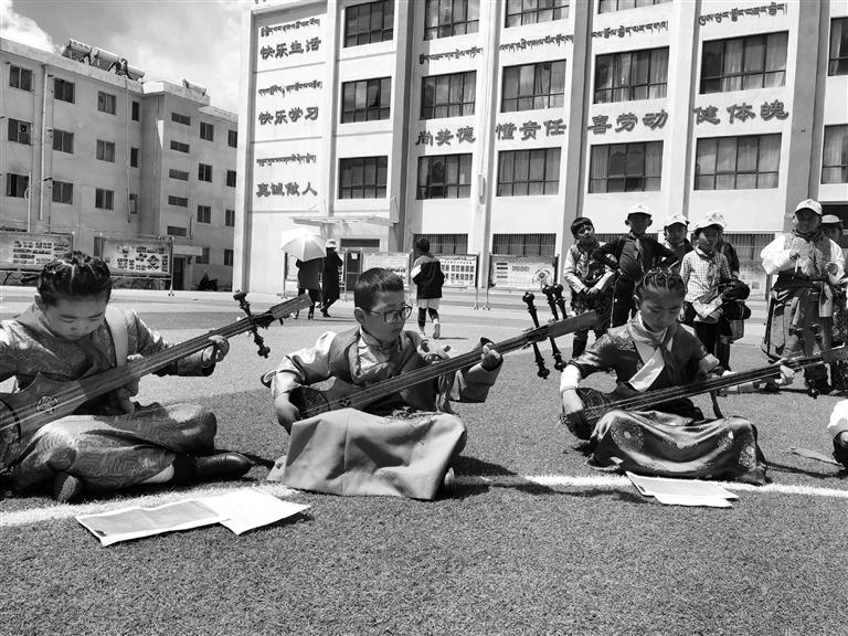 图为拉萨市第三小学学生围坐在操场上弹奏六弦琴. 记者 秦晓聪摄图片